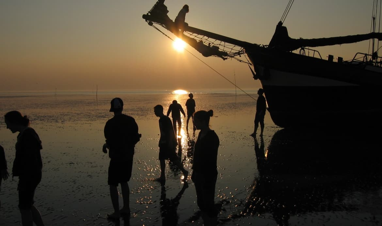 mensen staan op het wad bij zeilschip